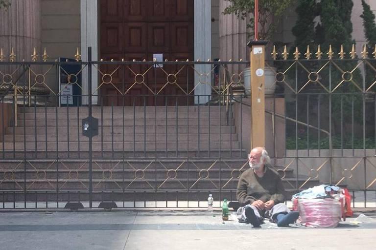 Um homem idoso, de cabelos brancos, aparece sentado na rua, recostado sobre as grades de um templo religioso. Ele tem consigo algumas garrafas plásticas e uma sacola com pertences.