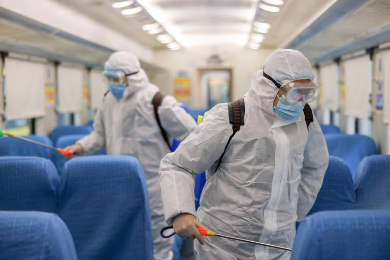 Com roupas de proteção que cobrem até a cabeça, dois funcionários fazem a desinfecção em meio a poltronas do trem