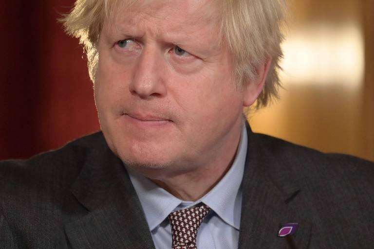 Boris, de paletó escuro e gravata marrom, olha para o lado