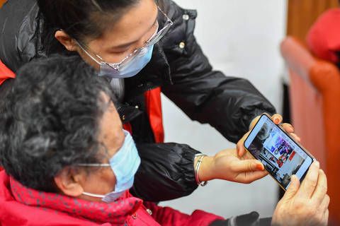 (210112) -- CHANGSHA, Jan. 12, 2021 (Xinhua) -- A volunteer teaches an elder how to film and view video with smartphone at Xiajiachong community in Tianxin District of Changsha City, central China's Hunan Province, Jan. 12, 2021. The community has invited volunteers to teach the use of smartphone to elders, helping them keep pace with modern society. (Xinhua/Chen Zeguo)