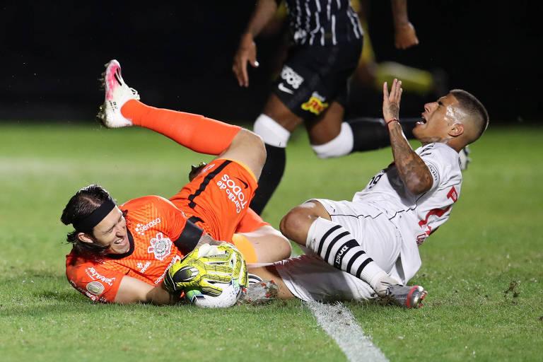 Goleiro agarra a bola em dividida com jogador do Vasco