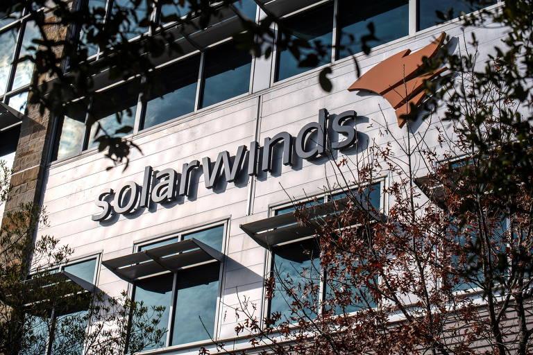 Fachada da sede da empresa, com galhos de árvores no primeiro plano