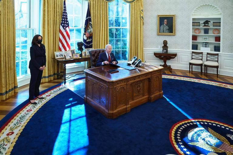 Joe Biden assina ordem executiva relacionada ao sistema de saúde, junto com sua vice, Kamala Harris, no Salão Oval da Casa Branca