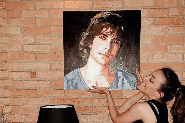 Irmã de Fiuk, Tainá Galvão ao lado de um quadro do cantor