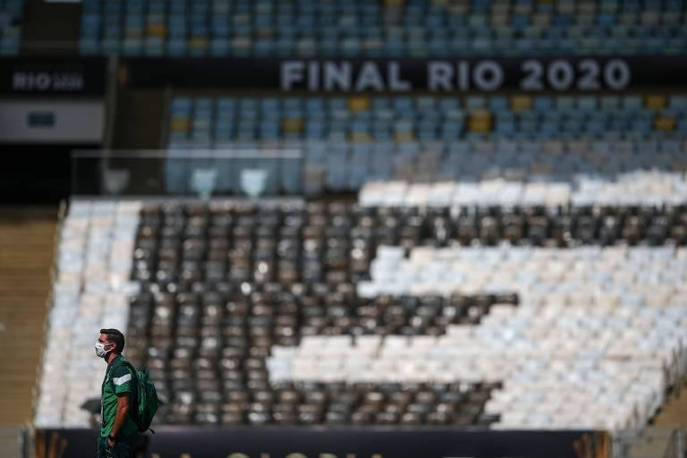 Homem de verde caminha em frente a arquibancadas vazias do Maracanã