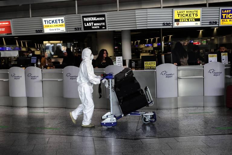 Pessoa de roupa branca cobrindo todas as partes do corpo e da cabeça empurra carrinho de malas em saguão de aeroporto