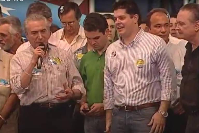 Homens em pé em discursam em palanque durante evento de campanha