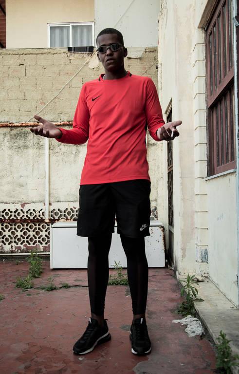 homem negro de blusa vermelha de manga comprida e óculos escuros