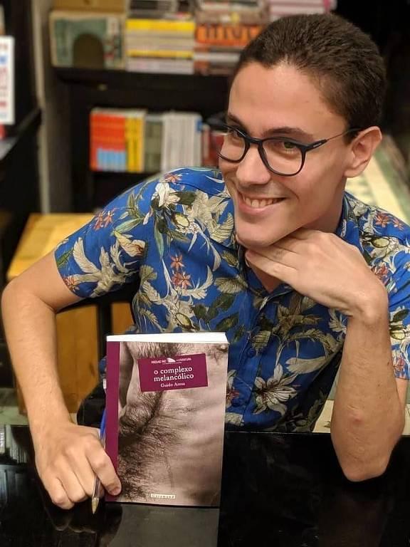 Homem posa para foto com livro sobre a mesa
