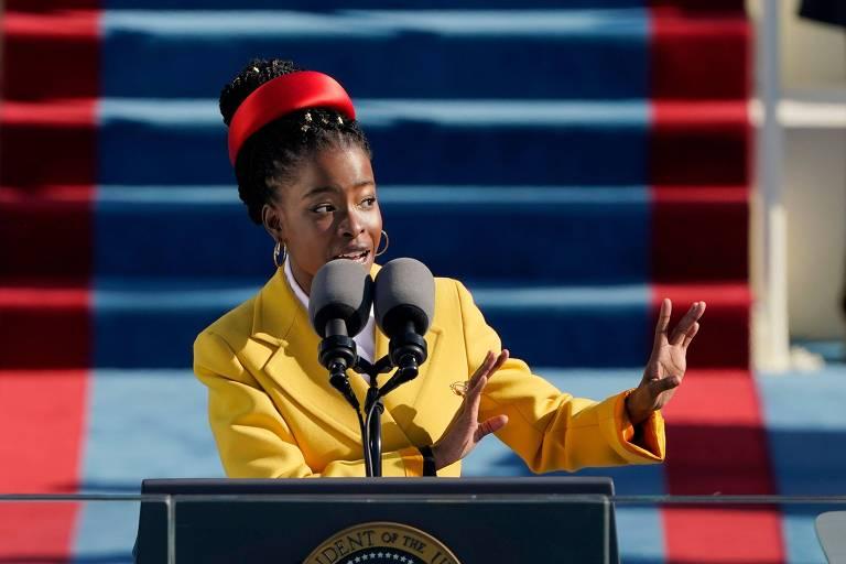 Jovem negra de jaqueta amarela fala ao microfone