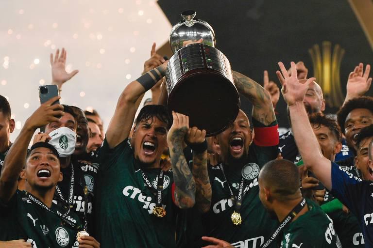 Gustavo Gomez (à esq.) ergue a taça da Libertadores junto com Felipe Melo