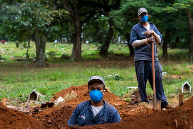 Dois homens, um dentro de um buraco até a altura do peito, e outro segurando uma pá ao lado, olham para a câmera. Eles usam macacão cinza e uma máscara comum. Atrás, há árvores.