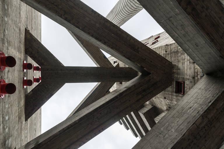A foto é feita do térreo para o alto e mostra as passarelas de concreto em forma de V ou seta que ligam dois prédios