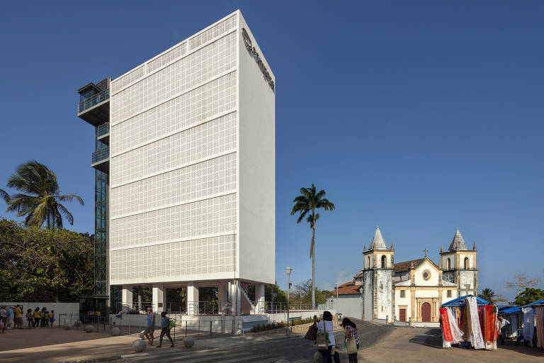 É uma construção branca, em forma de prisma retangular, que fica próxima a uma antiga igreja