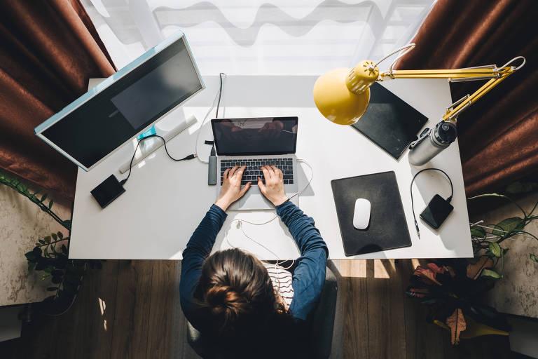 Mulher vista de cima trabalhando em uma mesa de trabalho com laptop, abajur e computador