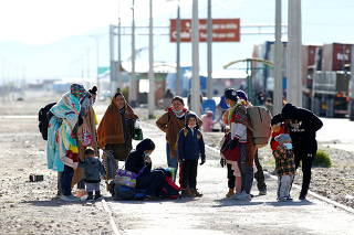 Venezuelan migrants gather after using an illegal crossing at the border with Bolivia in the Colchane area