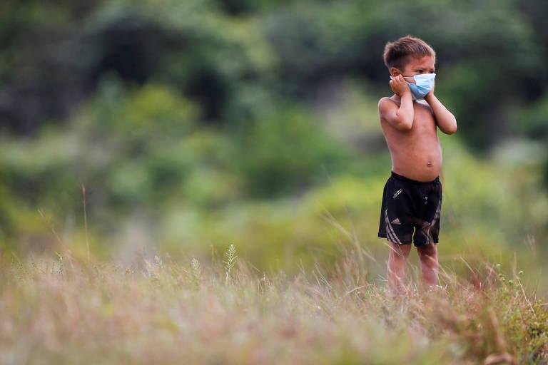 Em meio à relva e com árvores ao fundo, menino indígena usando bermuda preta e máscara cirúrgica observa a paisagem enquanto ajusta a proteção no rosto.