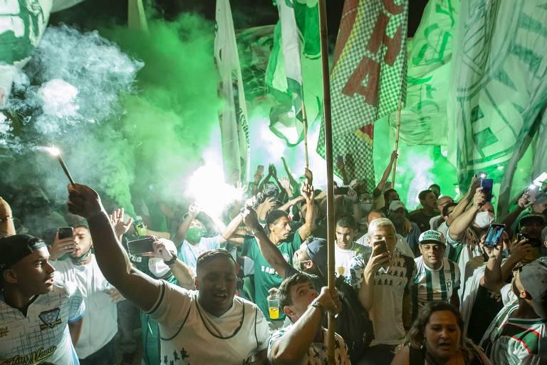 Torcedores aglomerados, a maioria deles sem máscara, durante embarque do Palmeiras no aeroporto de Guarulhos para o Qatar