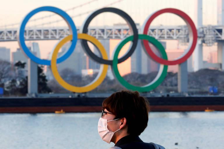 Pessoa de máscara em frente a anéis olímpicos em baía de Tóquio