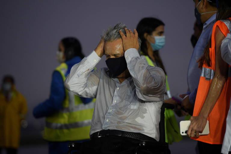 O presidente do Equador, Lenin Moreno, ajeita o cabelo na chuva durante a chegada da primeira leva de vacinas contra a Covid-19 em Quito
