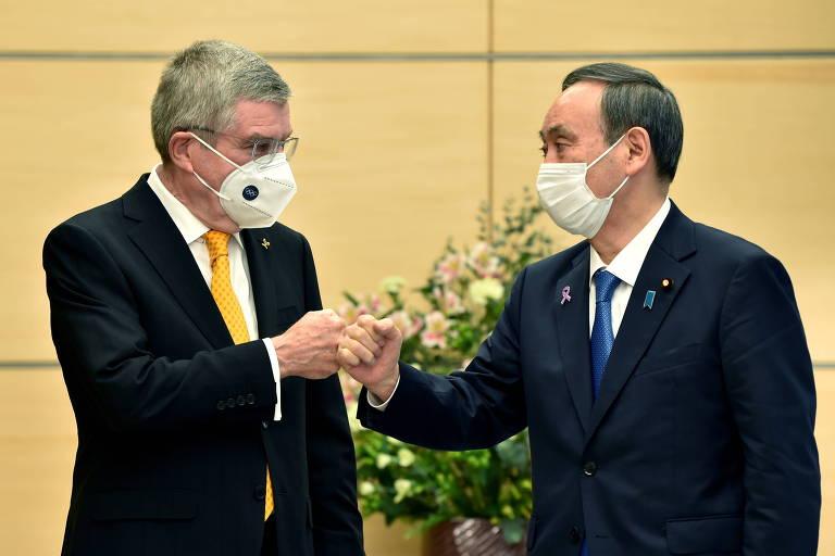 O primeiro-ministro japonês, Yoshihide Suga, e o presidente do COI, Thomas Bach, se cumprimentam