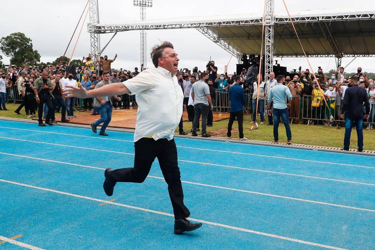 Bolsonaro é um homem branco de cabelos lisos e castanhos, com alguns fios grisalhos. Ele veste camisa de manga curta branca, calça preta e sapatos pretos. Ele corre com os braços para trás e boca aberta em pista azul de um centro de atletismo. Ele é observado por pessoas ao fundo, atrás de grades.