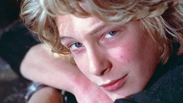 jovem loiro de olhos azuis encara a câmera