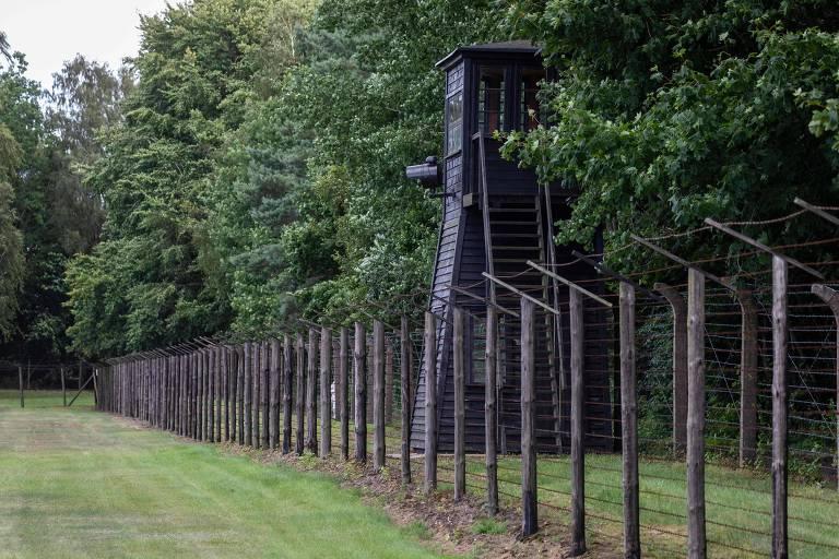imagem da alta cerca de arame preto ao redor do que restou do campo de concentração