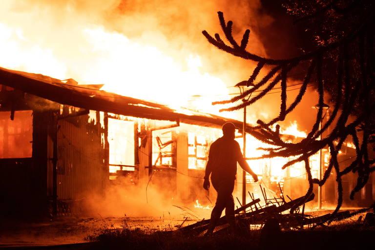 Vulto de pessoa caminhando ao lado de prédio tomado pelo fogo