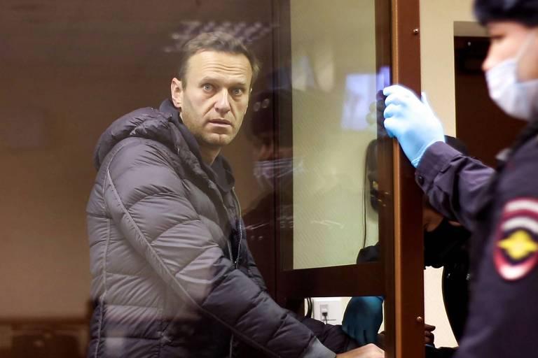 homem branco está atrás de uma parede de vidro em tribunal