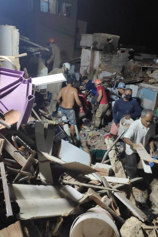 Quatro pessoas vasculham escombros de casa