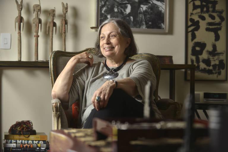 Vera sorri enquanto está sentada em cadeira, com o braço direito apoiado, próximo ao rosto