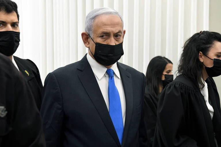 Ao centro, Homem de máscara e terno, com gravata azul; em cada um de seus lados, advogados podem ser vistos parcialmente