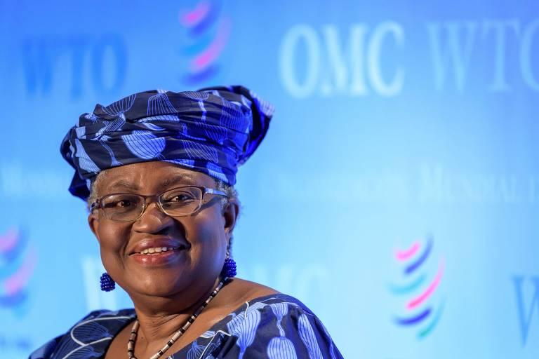 Mulher negra de óculos, brincos azuis, lenço azul estampado na cabeça amarrado em estilo africano e blusa da mesma estampa