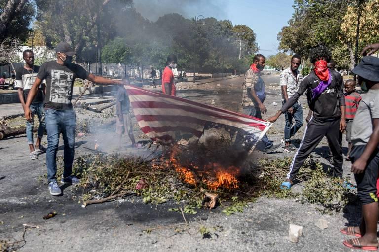 Manifestantes queimam uma bandeira americana em Porto Príncipe, durante um protesto para exigir a renúncia do presidente haitiano Jovenel Moïse