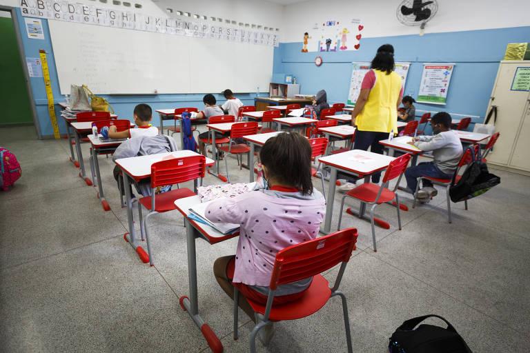 crianças sentadas em carteiras vermelhas em uma sala de aula com paredes azuis e brancas