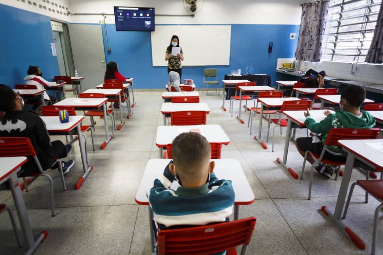 Fotografia colorida de uma sala de aula vista com câmera nos fundos do ambiente. A imagem retrata quatro fileiras de carteiras com poucos alunos nela para medidas de segurança contra a Covid. À frente, há uma professora em pé