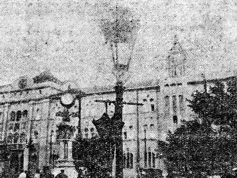 Reprodução da primeira foto publicada no jornal Folha da Noite (19 de fevereiro de 1921), em que vendedores ambulantes penduram guarda-chuvas nos braços dos lampiões de gás no centro da cidade