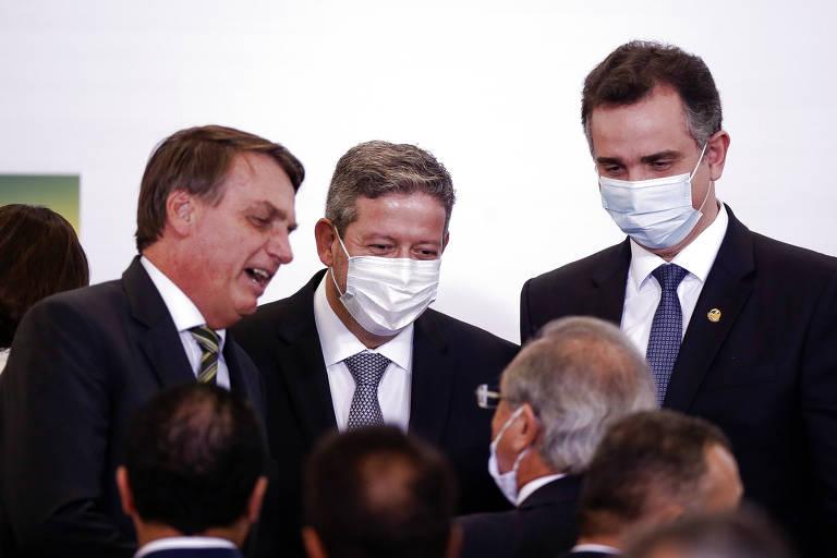 Três homens vestidos de terno e gravata escuros conversando e sorrindo