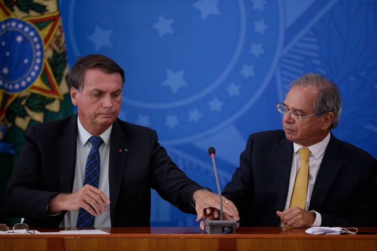 Sentados, Jair Bolsonaro faz menção de segurar a mão de Guedes, que olha para o presidente