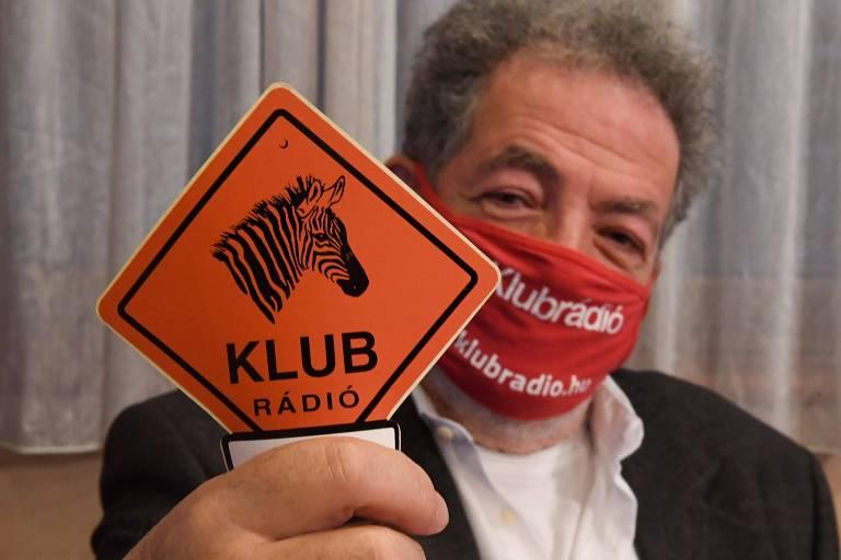 Homem de máscara vermelha segura placa com uma zebra e o nome Klubradio