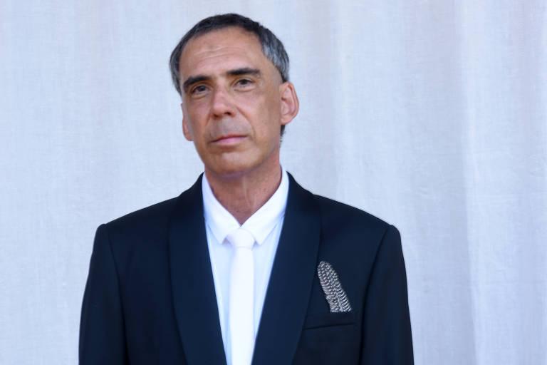 Vestindo paletó preto e camisa e gravata brancas, Arnaldo Antunes, moreno e grisalho, tem no bolso uma pena preta e branca, no lugar de um lenço