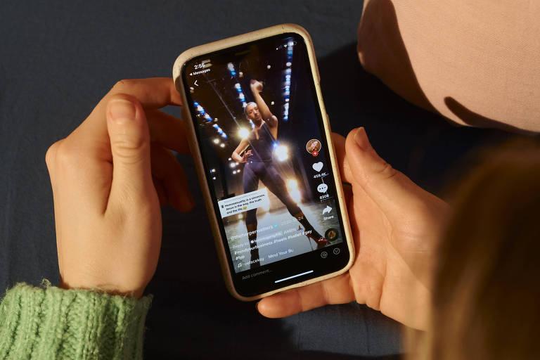 Mão branca segura celular que exibe vídeo de homem negro dançando