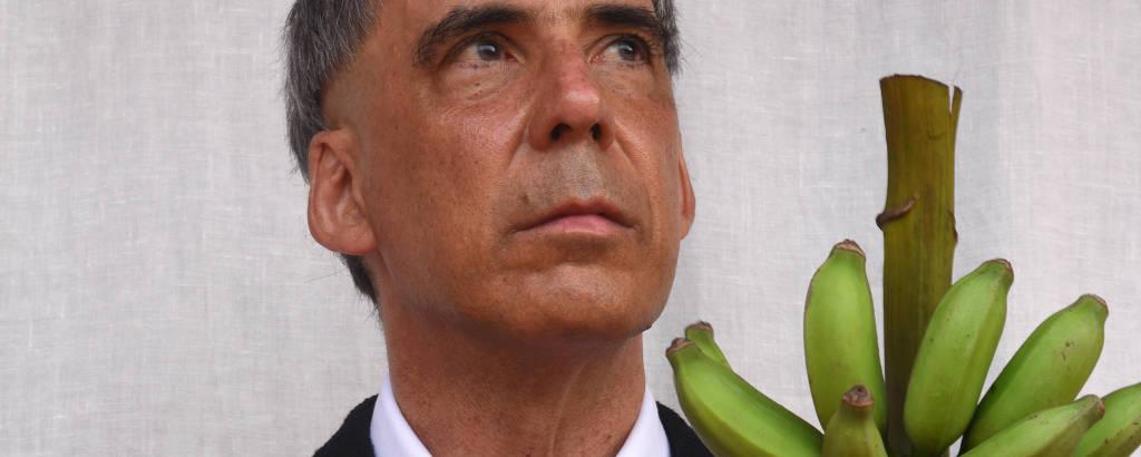 Vestindo paletó preto e camisa e gravata brancas, Arnaldo Antunes, moreno e grisalho, segura um cacho de bananas verdes