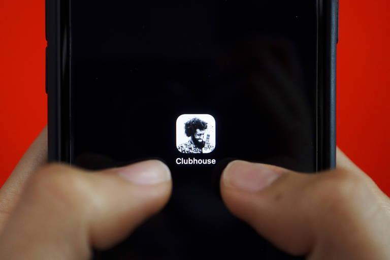 Uma pessoa segura um celular nas mãos com o aplicativo Clubhouse no centro da tela.