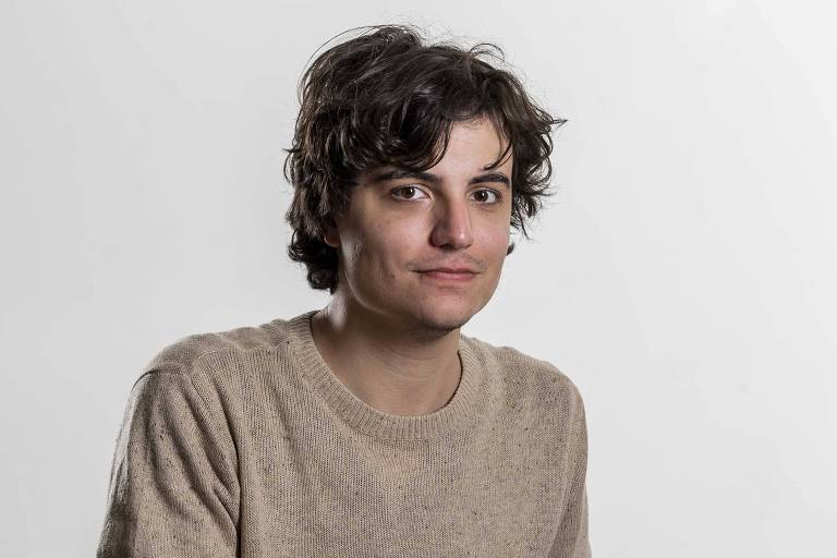 O chargista João Montanaro. Ele é jovem, tem olhos castanhos e cabelo cacheado a cobrir parte da testa. Tem pele clara e veste um agasalho bege.