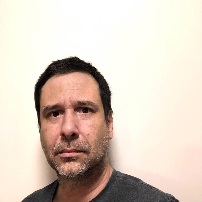 Leandro Assis. Ele tem cabelo preto curto, olhos castanhos, barba rala. Veste uma camiseta preta e aparece à frente de uma parede branca. Tem expressão séria.
