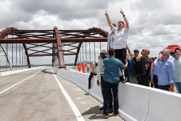 Bolsonaro é um homem branco de cabelos lisos e castanhos, com alguns fios grisalhos. Ele usa uma camisa branca e uma calça preta e está de pé na mureta de uma ponte. Ele está com os braços erguidos. Ao fundo, um grupo de homens o observa.
