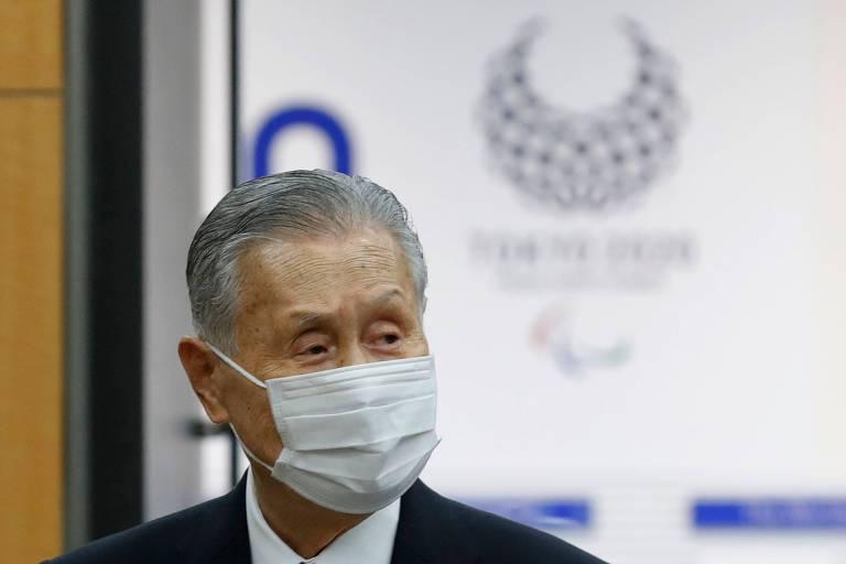 Yoshiro Mori de máscara em frente a painel com logo dos Jogos de Tóquio