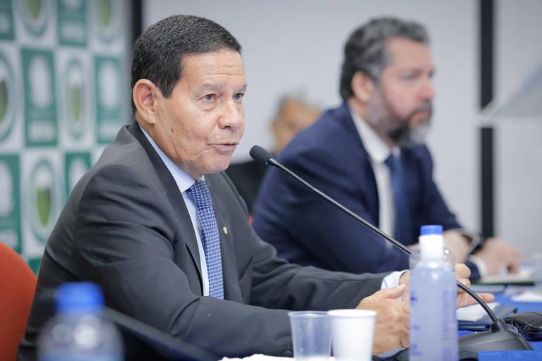 Vemos Mourão de terno cinza, camisa branca e gravata azul, falando a um microfone; ao fundo, meio desfocado, o então chanceler Ernesto Araújo